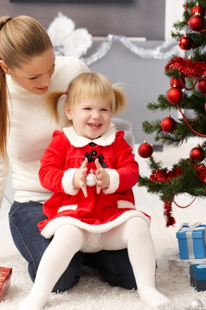 Little girl smiling happy at christmas in mothers' lap. photo
