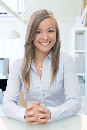 casual office: Happy casual woman sitting at office desk, looking at camera, smiling. Stock Photo