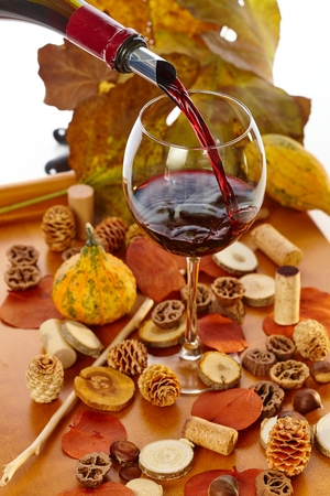 pineal: Pouring red wine from bottle to glass at vintage time among autumn decoration. Stock Photo