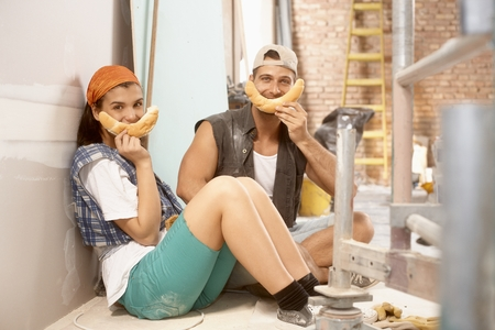 having a break: Happy young couple having fun at home renovation, preparing smiliy face from crescent roll, Stock Photo
