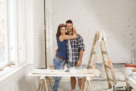 tinkering: Happy loving couple smiling and embracing in home under renovation, looking at camera.