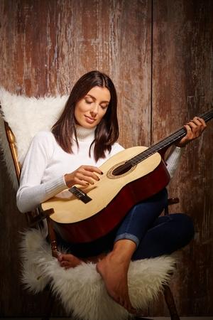 guitarra: Mujer atractiva joven que toca la guitarra con los ojos cerrados, sentado en el sillón sobre la pared de madera antigua. Foto de archivo
