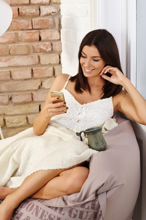 bean bag: Attractive young woman sitting in cosy bean bag chair, using mobilephone, smiling happy, relaxing.