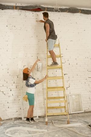 pintura en la cara: Joven pareja renovando su casa, pared de la pintura del hombre en escalera, pintura de la mujer que pasa.