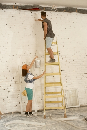 tinkering: Young couple renovating home, man painting wall on ladder, woman passing painting.