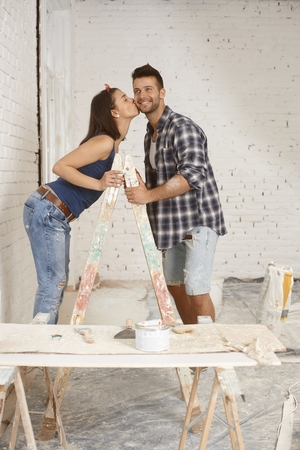 be kissed: Happy young couple kissing on ladder at home renewal.