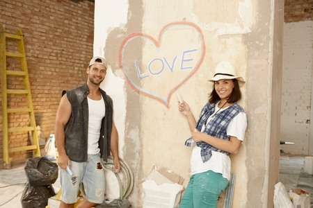 heart under: Young couple in new home under construction, standing by wall writing love and drawing heart on it, smiling happy.