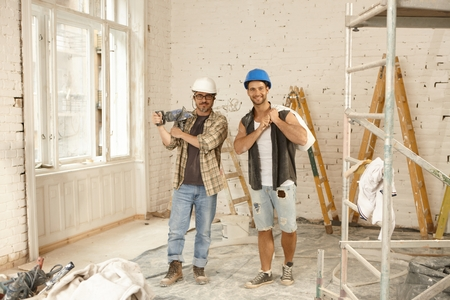 Happy workers standing at renovation site, smiling, looking at camera. Stockfoto