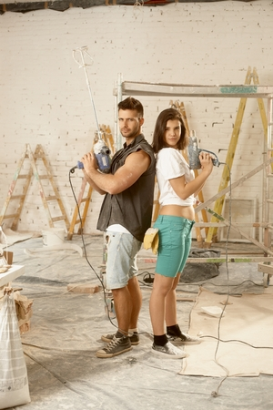 renewing: Determined young couple looking serious holding power drill, renewing home.