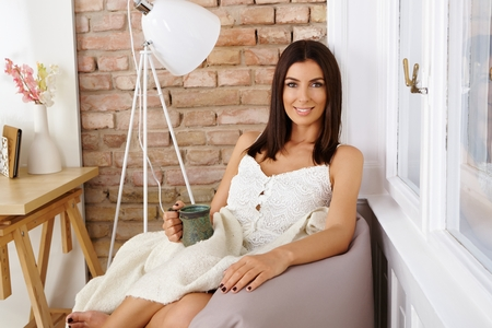 bean bag: Attractive young woman sitting at cosy home, smiling, drinking tea.