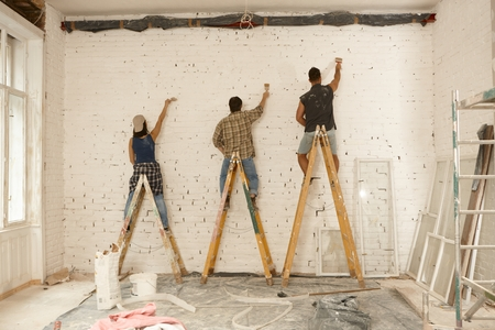 co work: Painter team working on renovation site, standing on ladder, painting wall by brush. Stock Photo