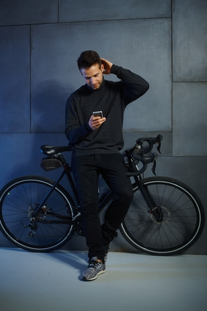leaning against: Young man using mobilephone, leaning against bicycle. Stock Photo