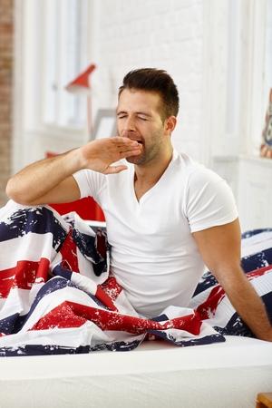 levantandose: Hombre joven en la mañana, bostezando en los ojos de cama cerrada. Foto de archivo