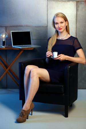 mujer sola: Atractiva joven rubia de negocios tomando un café-break, sonriendo, mirando a la cámara.