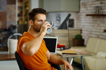 man style: Young man drinking tea at home, sitting at desk. Side view. Stock Photo
