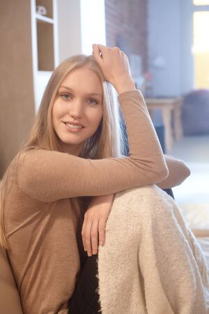 fantasize: Beautiful young nordic woman sitting at home, smiling, looking at camera.
