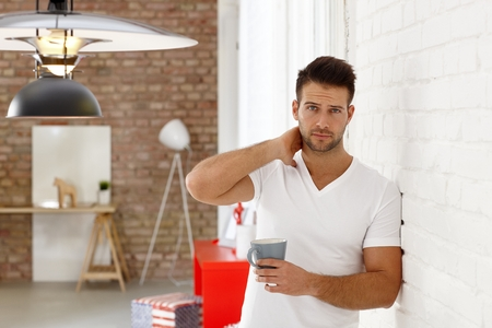 young guy: Sleepy young man leaning against wall, frowning with morning tea in hand. Stock Photo
