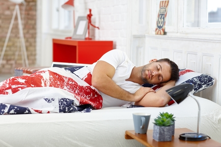 stubbly: Handsome young man sleeping in bed at home.
