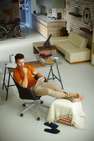 above 25: Young man sitting in retro home using tablet. Photographed from above.
