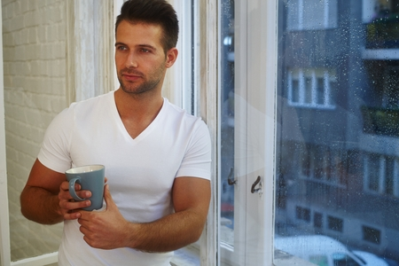 fantasize: Daydreaming young man standing front of window in rainy morning, holding mug of tea. Stock Photo
