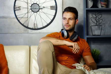 fantasize: Handsome young man sitting at sofa at home, daydreaming. Stock Photo