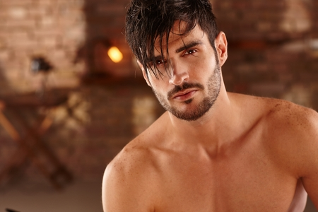 stubbly: Closeup photo of sexy latin man with bare chest, looking at camera.