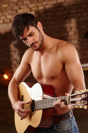 sexy guitar: Romantic young man playing the guitar with bare upper body. Stock Photo