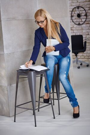image size: Busy young woman working writing notes to personal organizer. Stock Photo
