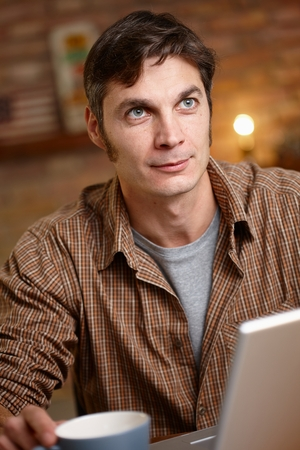 stockphoto: Daydreaming man sitting at table, looking up. Stock Photo