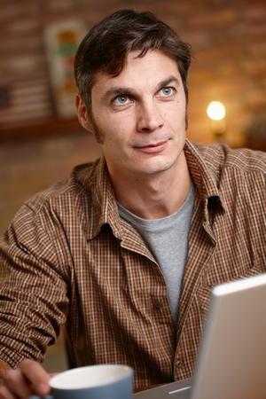 ojos azules: Soñando despierto hombre sentado a la mesa, mirando hacia arriba. Foto de archivo