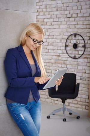 standing against: Young blonde woman using tablet computer, standing against wall.