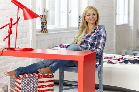 women in jeans: Cheerful young woman sitting at desk at home, smiling happy. Stock Photo