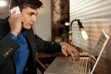 mobilephone: Busy businessman working with laptop computer, talking on mobilephone. Side view.