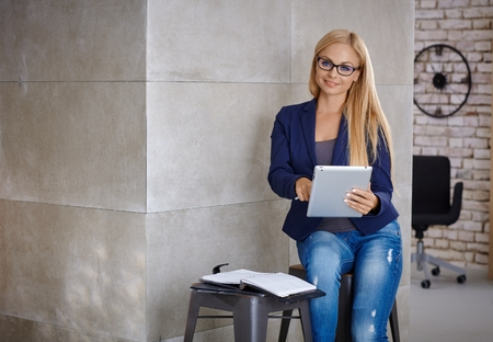 glasses eye: Busy blonde woman working with tablet, using personal organizer. Stock Photo
