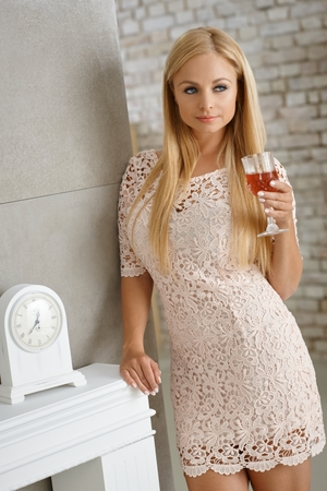 leaning against: Pretty blonde woman in mini dress holding a glass of wine, leaning against wall. Stock Photo
