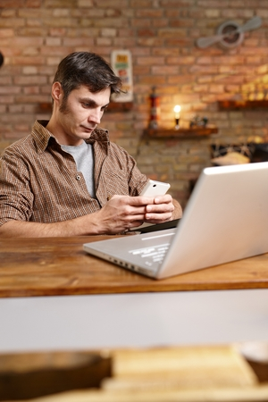 mobilephone: Casual young man using mobilephone, texting, sitting at desk, having laptop.