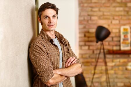 thirties: Thoughtful casual man leaning against wall arms crossed, looking away. Stock Photo