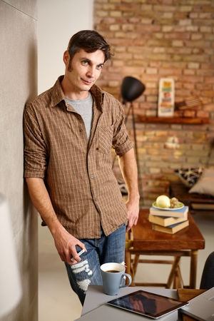 standing against: Casual man standing against wall at home, smiling, looking away. Stock Photo