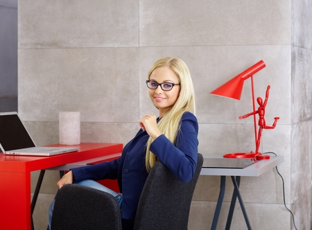 glasses eye: Beautiful young blonde woman sitting at desk, working with laptop computer, smiling at camera.