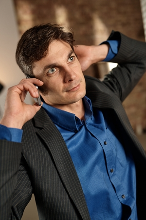 open collar: Thoughtful businessman talking on mobilephone, looking up, hand behind ear.