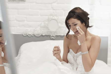 heartbroken: Heart-broken bride holding engagement ring, crying on wedding-day. Stock Photo