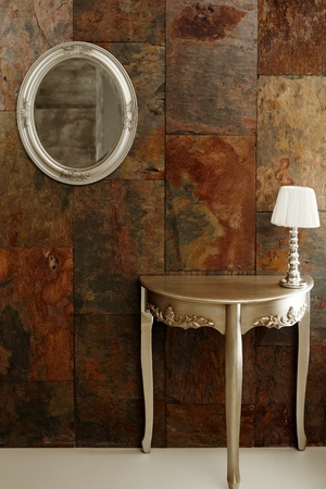 rusty metal: Stylish interior with mirror and dressing table front of rusty metal surface.