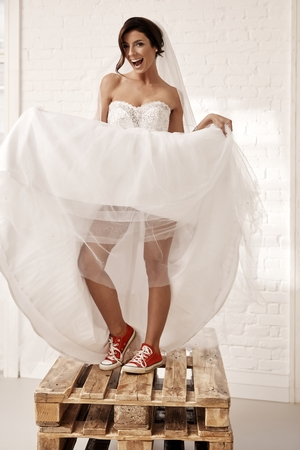 bride dress: Provocative bride in wedding dress and red sneakers smiling happy, lifting up dress.