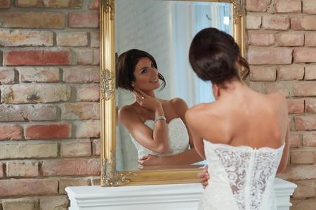 posing: Attractive young bride looking at herself in mirror, posing.