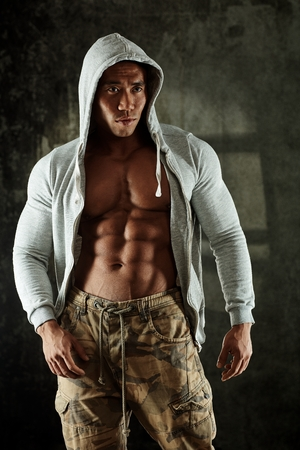muscle guy: Bodybuilder posing in hoody, showing perfect abdominal muscle. Stock Photo