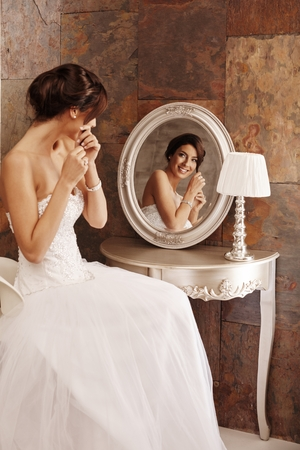25 to 30: Beautiful young bride fixing knot of hair in mirror, smiling happy.