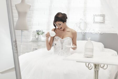 unlucky: Unlucky bride spilling coffee on wedding dress, looking shocked.