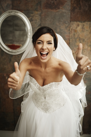 Happy bride in full glamour showing thumbs up. Foto de archivo