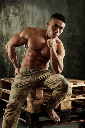 asian bodybuilder: Young asian bodybuilder sitting on pallet, thinking with bare upper body.