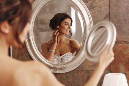 herself: Beautiful young bride preparing herself in mirror.